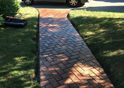 Front walkway with a beautiful herringbone brick impression with fieldstone patio